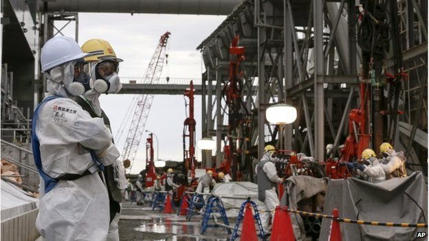 Workers stand by as others handle machinery and pipes which will be used to create a frozen underground wall to surround the crippled reactor buildings at Tokyo Electric Power Co.'s Fukushima Daiichi Nuclear Power Plant in Okuma, Fukushima Prefecture, northeast of Tokyo, Japan, Wednesday, 9 July 2014.