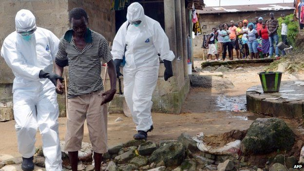 Nurses wearing protective suits escort a man infected with the Ebola virus to a hospital in Monrovia, Liberia - 25 August 2014