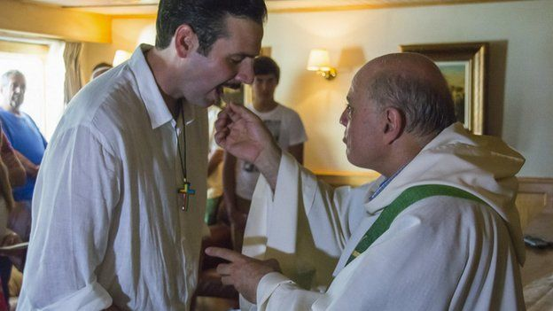 Chris Catrambone and priest at the mass on board the Phoenix