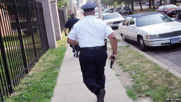 A Baltimore police officer runs with his gun drawn.