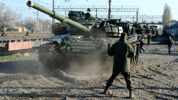 Russian soldiers unload T-72 tanks from a train near the Crimean capital Simferopol, on March 31, 2014