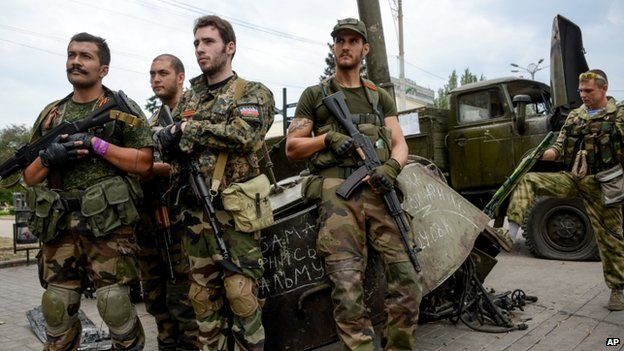 French volunteers on rebel side stand with destroyed Ukrainian equipment