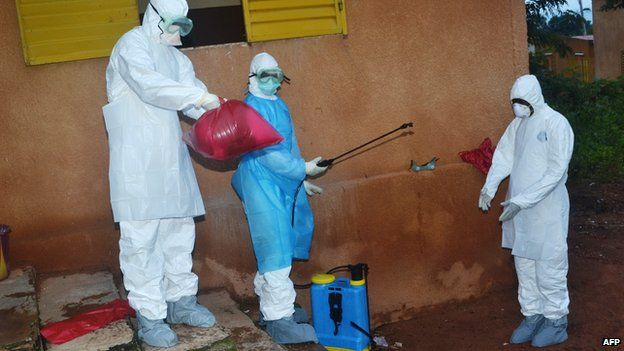 Health workers take off their protective suits after finishing disinfecting areas at the Pita hospital on August 25, 2014