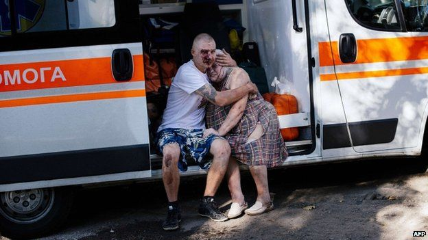 An injured man hugs a woman as they sit in ambulance after a shelling attack on Donetsk (23 August 2014)