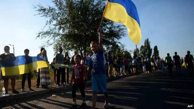 Ukrainian loyalists hold their flag as they rally at the last checkpoint on the eastern side of Mariupol (picture from 30 August)