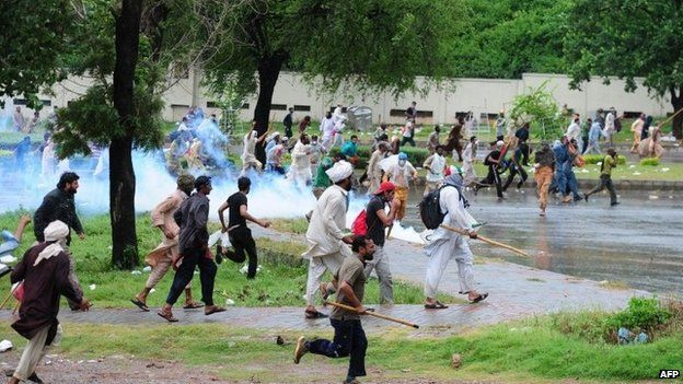 """Pakistani opposition protesters run towards police during clashes near the prime minister""""s residence in Islamabad on September 1, 2014."""