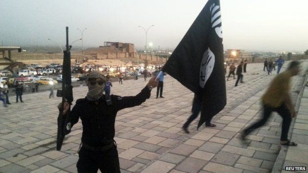 File photo: A fighter of Islamic State (IS) holds an IS flag and a weapon on a street in the city of Mosul, 23 June 2014
