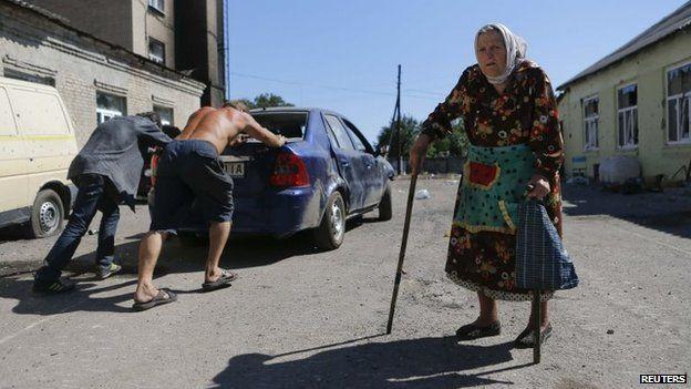 People push a broken-down car past a woman in the eastern Ukrainian town of Ilovaysk, 31 August 2014