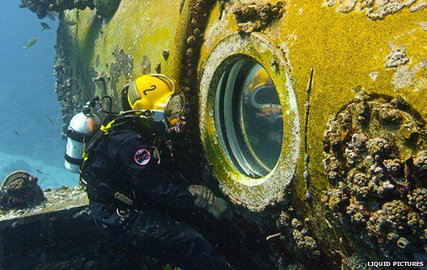 Diver looks through porthole