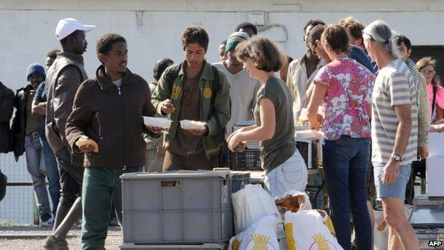 Members of an NGO distribute food to migrants in Calais (5 August 2014)