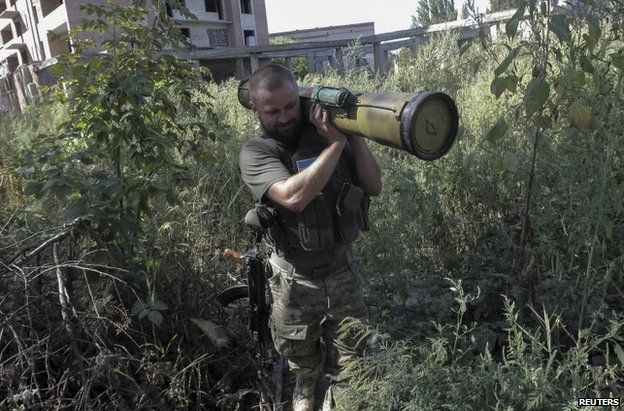 A Ukrainian policeman removes a weapon found in Sloviansk, Donetsk region, 2 September
