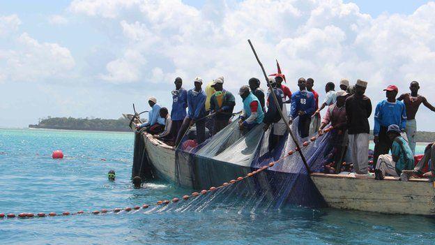 Fisherman pulling nets on a wooden boat off Tanzania