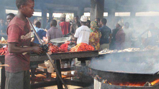 A man prepares fish dishes at Dar es Salaam's fish market, Tanzania