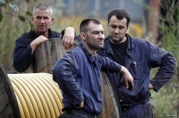 Miners stand outside the Raspotocje coal mine in Zenica, 5 September