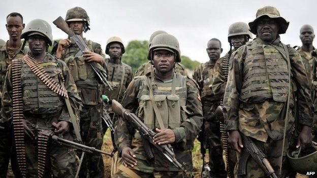 A handout picture taken and released on 31 August 2014 by the African Union-United Nations Information Support Team shows Ugandan soldiers, as part of the African Union Mission in Somalia, preparing to advance on a town in the Lower Shabelle region of Somalia
