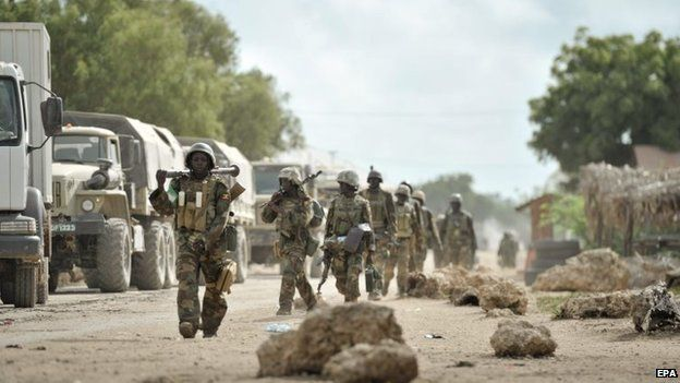 A handout photograph made available by the African Union Mission in Somalia showing Ugandan troops, as part of the African Union force, marching through the town of Golweyn after having liberated it from al-Shabab in Somalia's Lower Shabelle region on 30 August 2014