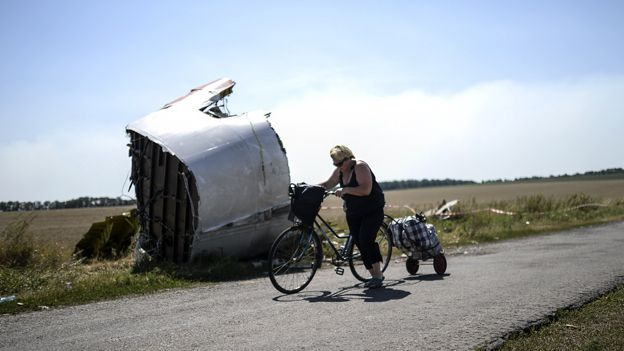 Woman cycles past wreckage of MH17 in a field in Ukraine