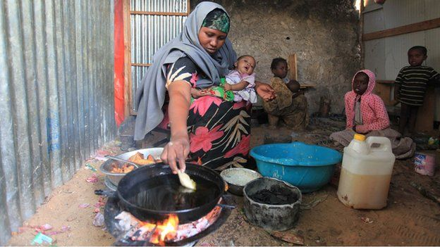 Faduma Aden Mohamud holding a baby as she cooks samosas in her house in a displacement camp in the Somali capital, Mogadishu