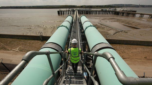 Worker walks between pipes at Thames Gateway Water Treatment Works