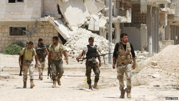 Free Syrian Army fighters walk together in the southern part of Maarat al-Nouman, Idlib province (July 2014)