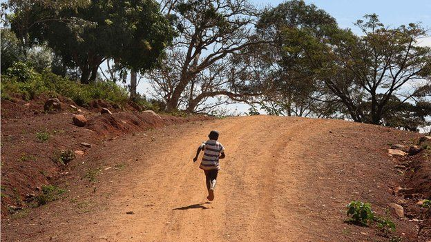 A boy runs along a dirt road on 12 January 2008 in Kogelo, western Kenya