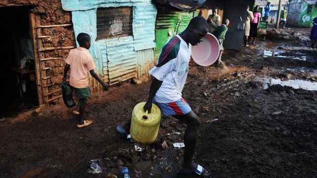 A man carries a bucket of water for washing as he steps over a muddy path in Nairobi's Kibera slum on 4 May 2011