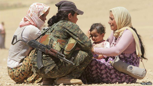 Displaced people from the minority Yazidi sect, who are fleeing violence from forces loyal to the Islamic State in Sinjar town, get help from a member of the Kurdish People's Protection Units on the outskirts of Sinjar mountain (10 August 2014)