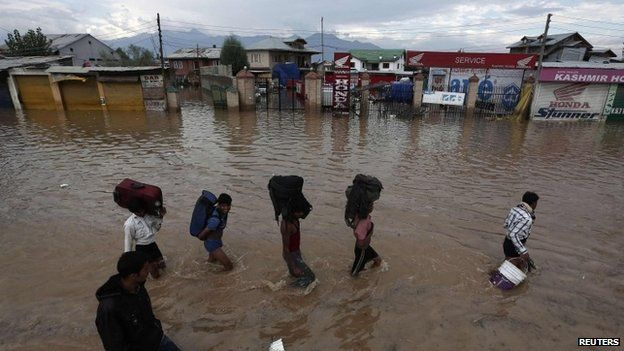 Kashmiri people wade through a flooded street as they move towards higher ground in Srinagar September 9, 2014