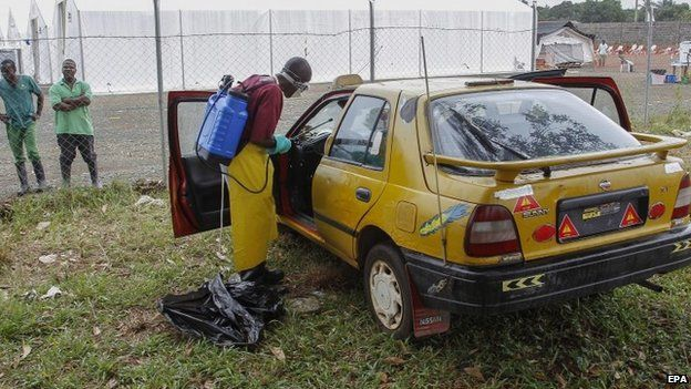 Liberian health worker disinfects taxi (9 September 2014)