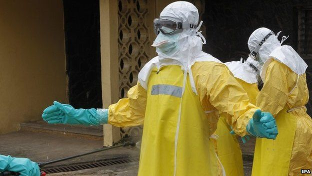 Health worker being sprayed with disinfectant