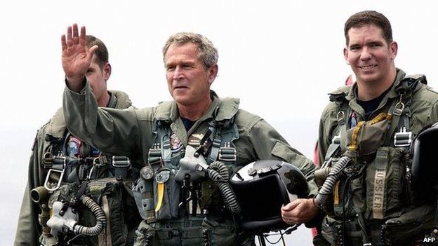 """Bush declares """"mission accomplished"""" on the desk of a US aircraft carrier"""