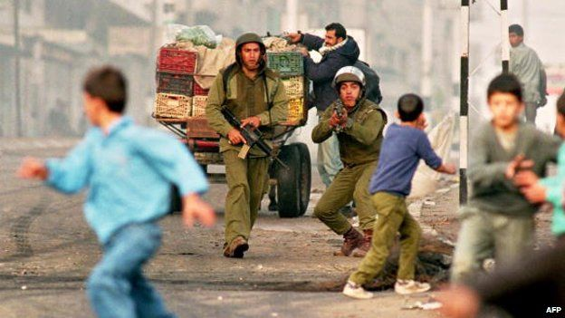Israeli soldiers confronting stone-throwing Palestinian boys in Gaza city in 1993