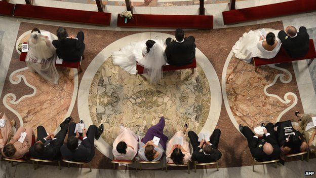 Brides and grooms sit during their wedding ceremony celebrated as part of a mass by Pope Francis at St Peter's basilica on 14 September 2014 at the Vatican