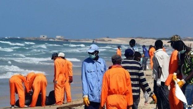 Rescuers collect the bodies of African would-be migrants that were washed up on the shore of al-Qarboli, east of Tripoli, Libya, 25 August 2014.