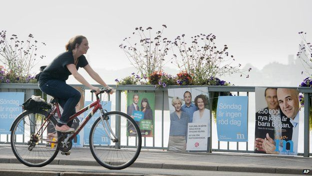 A cyclist in Stockholm passes election posters for the two largest parties in Sweden