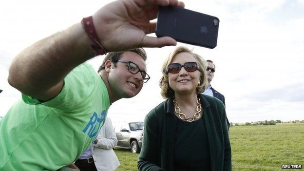 Former US Secretary of State Hillary Clinton poses for a photo with a supporter at the 37th Harkin Steak Fry in Indianola, Iowa 14 September 2014