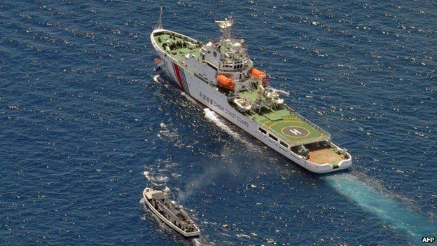 A China Coast Guard ship (R) and a Philippine supply boat engage in a stand off as the Philippine boat attempts to reach the Second Thomas Shoal, a remote South China Sea a reef claimed by both countries, on 29 March 2014