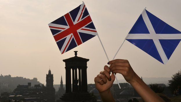 A union flag and saltire held up in front of the Edinburgh