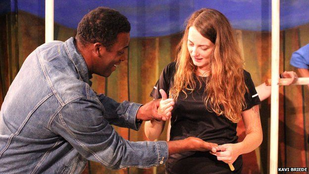 Sophie and a male actor during rehearsal. He is holding both her hands and leaning in towards her.