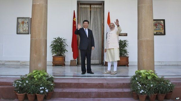 Indian Prime Minister Narendra Modi and visiting Chinese President Xi Jinping wave to the media before a meeting in New Delhi, India, Thursday, Sept. 18, 2014.