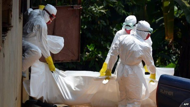Liberian Red Cross health workers, wearing protective suits, carry the body of a 18-old-month baby, a victim of the Ebola virus in a district of Monrovia, 12 September 2014