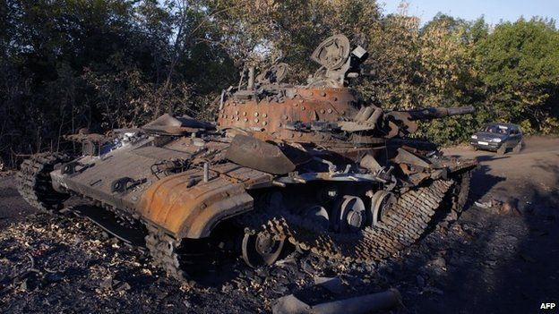 A car drives on September 19, 2014 near burnt military vehicles and unexploded ammunition following the recent bombing of a Ukrainian camp near the village of Dmytryivka in the region of Luhansk
