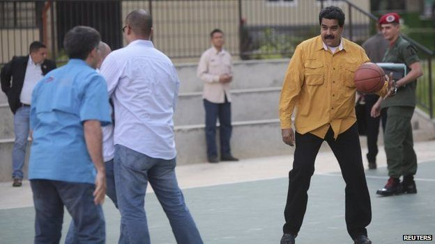 President Nicolas Maduro plays basketball during a ceremony where government houses are distributed to low-income beneficiaries in Caracas in this handout picture from 5 September 2014