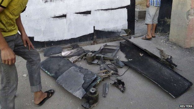 A man inspects the remains of what Islamist State militants say was a US drone that crashed in Raqqa - 23 September 2014