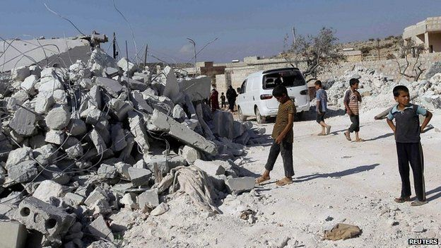Residents inspect buildings damaged by US-led strikes in northern Syria - 23 September 2014