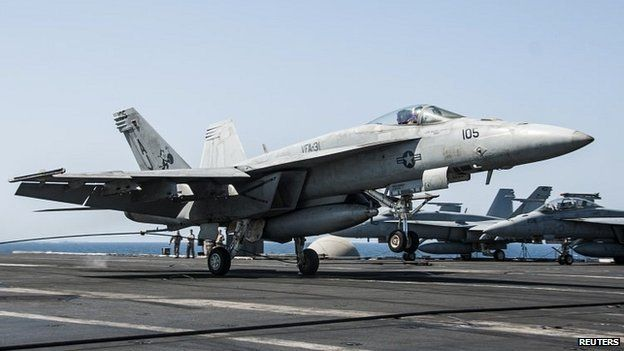 A US Navy F/A-18F Super Hornet landing aboard the USS George HW Bush after conducting air strikes on Islamic State militants - 23 September 2014