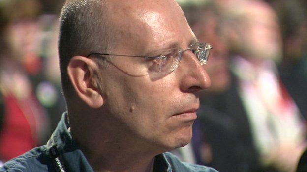 A man watches Harry Smith's speech