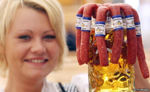 Oktoberfest waitress with tankard containing beer and sausages
