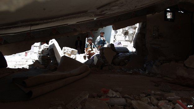 Yemeni children sit amid the debris of their house