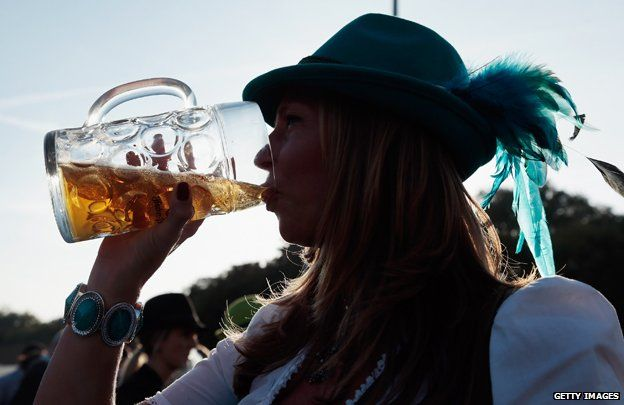 Woman in silhouette drinking from litre jug of beer at Oktoberfest